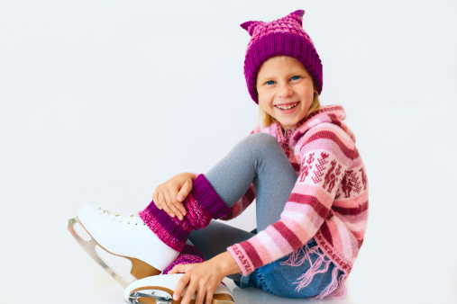 cheerful girl sitting on ice skates